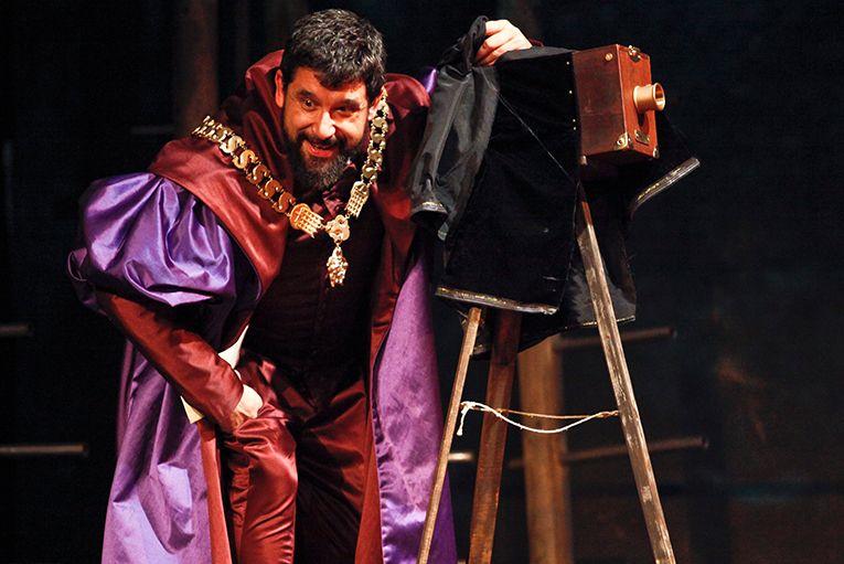 Actor teatro con ropa de época y cámara de fotos antigua