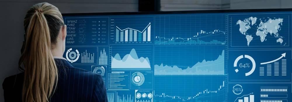 Big Data. Woman looking at large screen with many charts, graphs, data.
