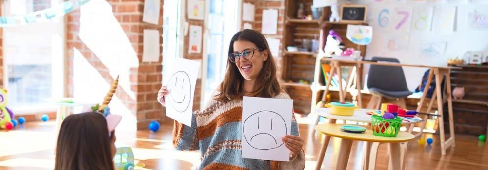 Educación, enseñanza inglés. Una profesora de infantil enseña emociones a una niña.