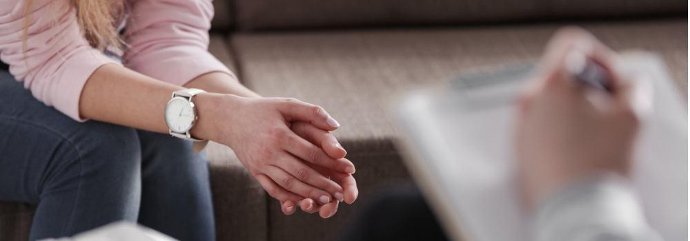 Psicología. Un psicólogo apuntando y las manos de una mujer de cerca.