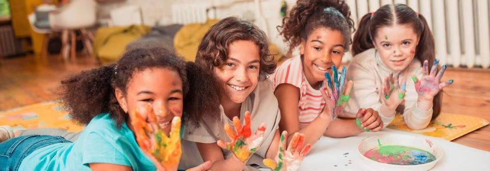 Educación, plástica infantil; 4 niñas pintando con los dedos con las manos pintadas levantadas sonriendo