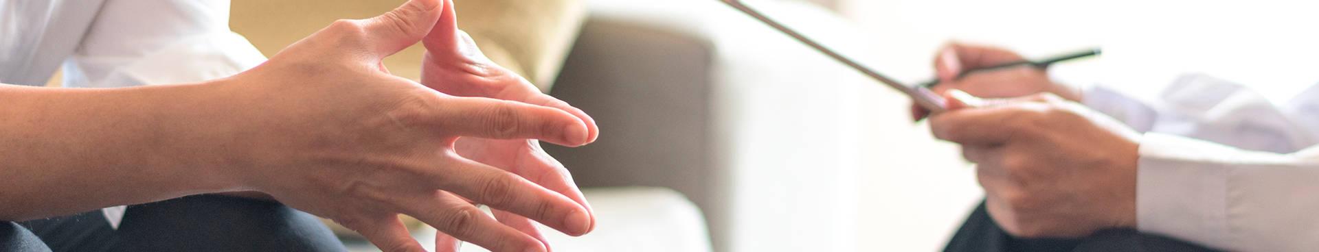 Psicoterapia; un hombre ansioso mira a su terapeuta mientras evalúa en un papel