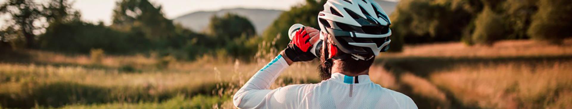 hidratación en el deporte; un ciclista descansa para en el campo para beber agua